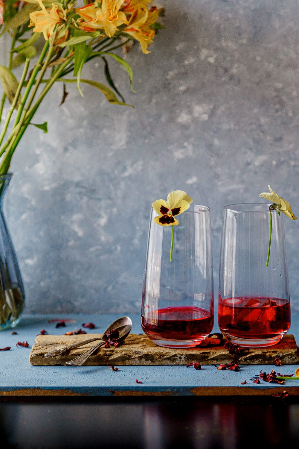 Hibiscus chilled Karkade tea served in tall delicate glasses with edible flowers